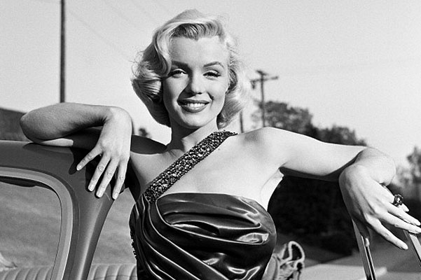 """LOS ANGELES - 1953:  Actress Marilyn Monroe leans on a Singer Automobile as she poses for a portrait on the set of the movie """"How To Marry A Millionaire"""" which was released in 1953. (Photo by Frank Worth, Courtesy of Emage International/Getty Images)"""