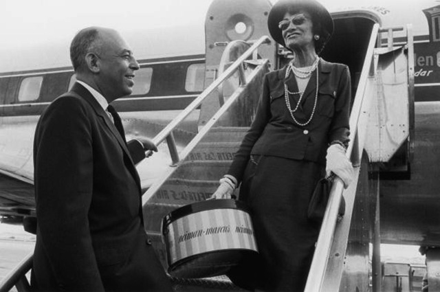 1957:  French fashion designer Coco Chanel says goodbye to American department store executive Stanley Marcus as she boards an airplane in Dallas, Texas. Chanel had been visiting for the opening of a new Neiman-Marcus store. She holds a package from the store.  (Photo by Shel Hershorn/Hulton Archive/Getty Images)